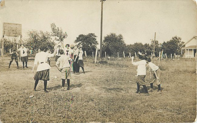 Children playing basketball in a field