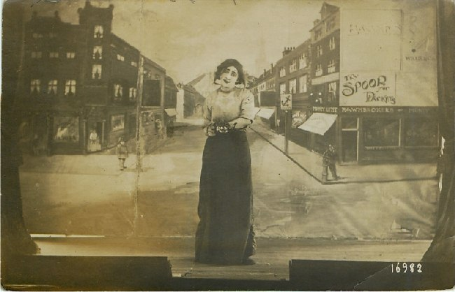 On Stage in Dress Holding a Teapot with Town Backdrop