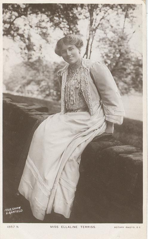 Miss Ellaline Terriss sitting on a wall Postcard